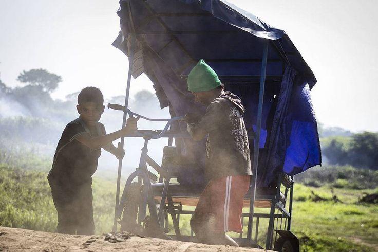 """Guamal, Magdalena.   Ph : Carlos Bernate @tejiendo_memoria14 / Tejiendo Memoria  Niños laboran a la orilla del río Magdalena, llevando mercancía en los """"Ciclo-Taxis"""", para cargar los """"Johnson"""", pequeñas canoas motorizadas que se dirigen al corregimiento de pajaral.  #TejiendoMemoria #ContandoHistorias #Guamal #Magdalena #Colombia #HistoriasDeMiAldea #VidaCotidiana #HardWork #child #childhood #children  #everydaylatinamerica #everydayeverywhere #everydaymacondo #ig_colombia"""