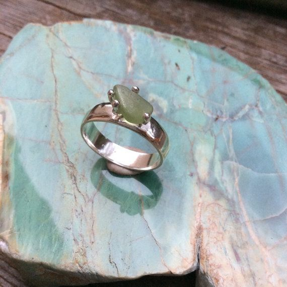This super shiny, 4mm wide sterling silver band with sterling silver claws features a seaweed green coloured glowing sea glass. Due to the randomness of each piece of sea glass, this ring is a totally unique, one of a kind creation.    The band is 100% sterling silver, with a half round profile, 4 mm wide, and the frosted green sea glass gem is approx 12mm by 6mm. The size of this ring is UK size R 3/4, US size 9.  Free shipping included.         #sterlingsilver #sterlingsilverrings…
