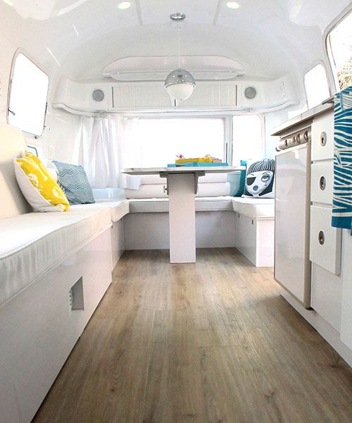 """Sneak Peek: Amelia the Airstream. """"Normally Airstream interiors are a cool aluminum tone, but the sleek high gloss white enamel we used keeps the small space bright and airy for summer """"glamping"""" (glamourous camping) travel. The floors are a faux weather wood vinyl. Keeping the weight of the camper light was important when planning the space."""" #sneakpeek"""