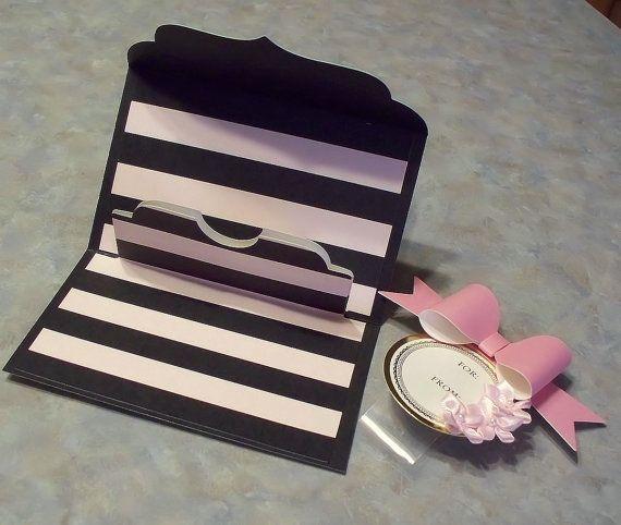 Ce porte carte/argent-cadeaux pop-up est conçu pour ressembler à un sac à main dembrayage. Le rabat et létiquette ont accentuant la magnifique feuille dor qui est à prévoir avec des produits Anna Griffin !  La carte a été faite à laide de produits de sa collection gracieuse Giftables II et mesures environ 5 « x 3 », la fermeture & 8 « x 5 », lors de louverture complète.  Le gros noeud rose, les fleurs en satin roses & tag sont attachés à une bande de ventre acétate transparent, c...