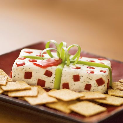 Christmas Package Cheese~   Ingredients:8 ounces of cream cheese (softened),1/2 tsp. dried dill,1/4 tsp. garlic powder,1/8 tsp. salt,Scallion,Red bell pepper.              ~Mix dill, garlic powder, and salt into softened cream cheese.            Pack the mixture into a rectangular container lined with plastic wrap (you can reuse the cream cheese box).           Refrigerate it for at least 3 hours. Before serving, add scallion bow, red pepper dots and gift tag.
