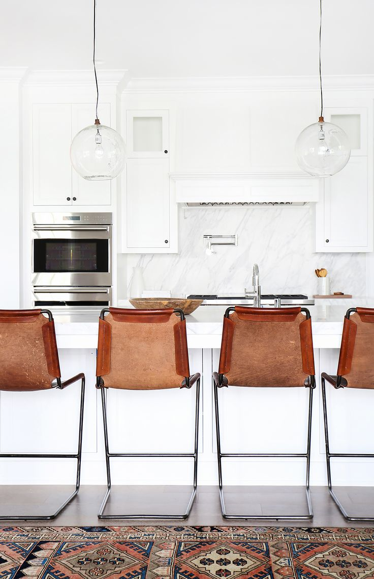 A gorgeous white kitchen with marble backsplash and pendant lights above leather bar stools and island