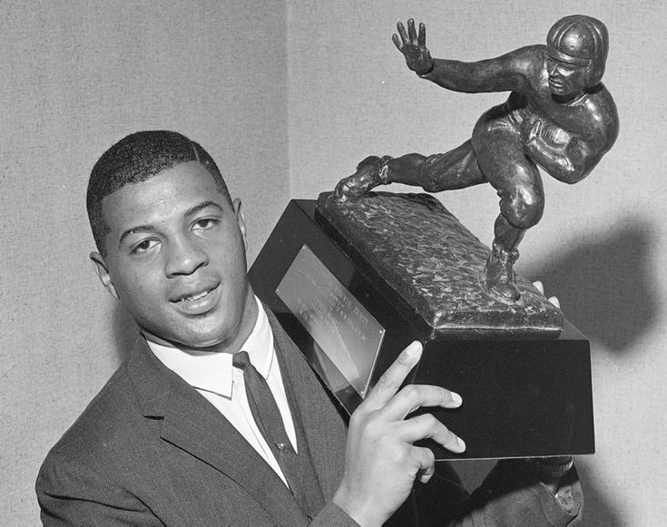 Now that's a hefty trophy! Ernie Davis of Syracuse University holds the Heisman Memorial Trophy at a dinner at the Downtown Athletic club in New York. The 1961 Heisman trophy winner from was the first African American to be awarded honor.