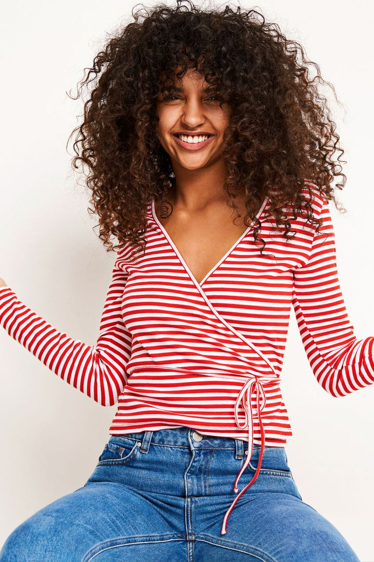 We are styling this candy stripe wrap top with jeans or a dress. The long sleeve wrap top has stretch, a v-neckline and is semi-fitted. Centre back length is 61 cm on small. The model is wearing a size small.
