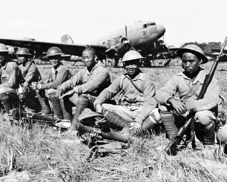 Chinese soldiers wait with their weapons to board Douglas C-47 Skytrains of the U.S.Tenth Air Force to return to China during the Burma Campaign. With the Ledo Road now almost fully secured,...