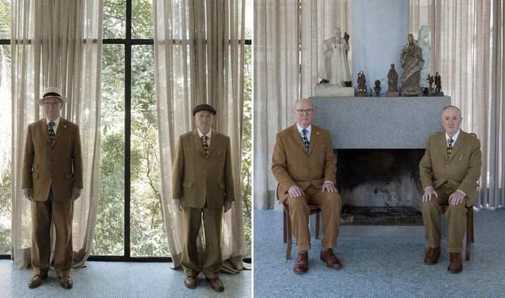 Gilbert & George standing, and posing next to Lina Bo Bardi's fireplace, 2012