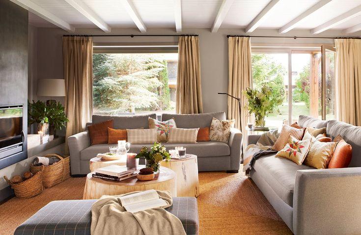 Salón en tonos grises y marrones con amplios ventanales