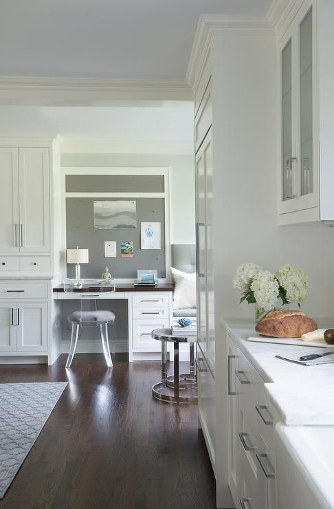 Beautifully design open plan dining room features a white built in desk fitted with nickel pulls and a wood desk top seating a lucite Klismos chair and positioned beneath a gray inset pin board framed by light gray walls.