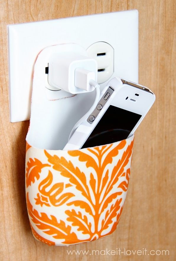 Take an old lotion bottle (this is a Johnson  Johnson baby shampoo bottle) and cut it to fit around an outlet and plug.  Select some fabric and Mod Podge it on.  Instant electronic device holder, clear counters!