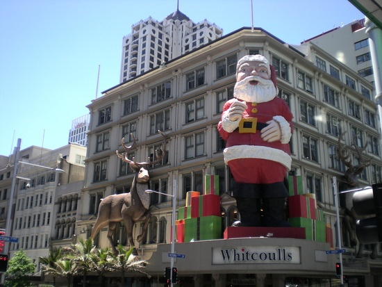 This Santa has been on display in Auckland City for about 50 years.  He used to be put up on the old Farmers building, but when that was sold and demolished it was purchased by Whitcoulls and now he is constructed on their big building in Queen Street each year.  His eye winks and his finger moves.