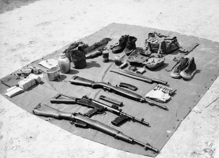 Specialised jungle equipment as carried by British forces during the Malayan Emergency:  Weapons - Lee Enfield Rifle No.5 Mk.I, Owen SMG and an M1 Carbine. Other equipment - parang, first aid kit, pair of jungle boots, pair of hockey boots (for wearing at night), water bottle, mess tin and jungle ration pack (consists of cheese, jam, biscuits, ginger pudding, steak, liver and bacon, tea, sugar, milk,  sweets, chewing gum, toilet paper, salt and one paludrine tablet). © IWM (MAL 300)