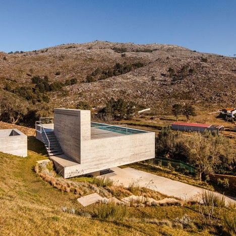This concrete house in northern Portugal by local studio Carvalho Araújo features an overhanging roof dedicated to a narrow swimming pool