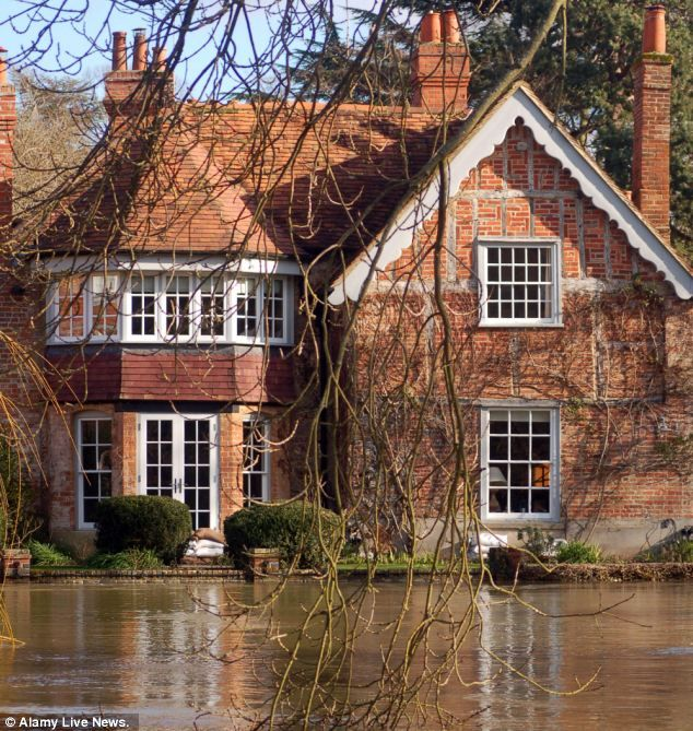 Besieged: Floodwater can be seen lapping against the detached property in Goring-on-Thames, Oxfordshire