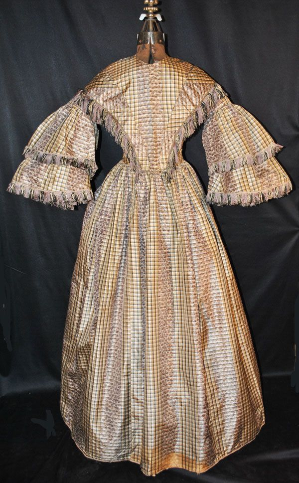 "c.1850's CIVIL WAR SILK PLAID LADIES GOWN WITH PAGODA SLEEVES FOR STUDY OR DISPLAY. A fetching 1850's Civil war era brown, black, cream and tan plaid silk gown. The bodice is piped at collar, armscyes at drop shoulder are also piped. ebay seller oldthreads; bodice lined in white cotton; skirt lined in brown cotton; front hook & loop closure; one hidden side pocket; 4 whale baleen stays; cartridge pleated skirt; all hand sewn; bust: 32""; waist: 25"" length:: 57.5""; hem width: 143"""
