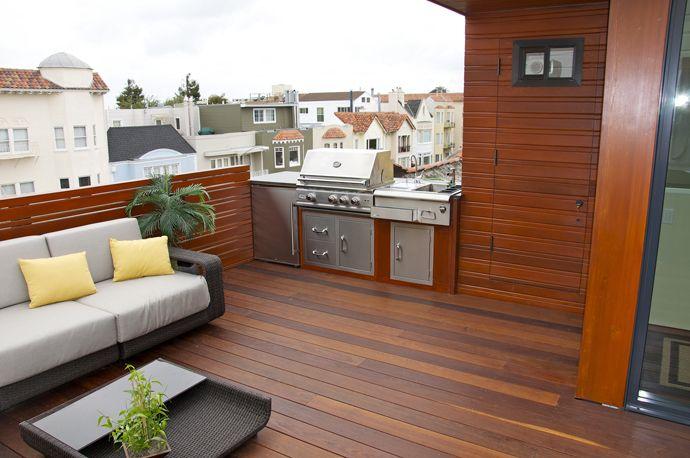 立派な屋外用BBQグリルのあるウッドデッキの屋上テラスの屋外リビング・ダイニング