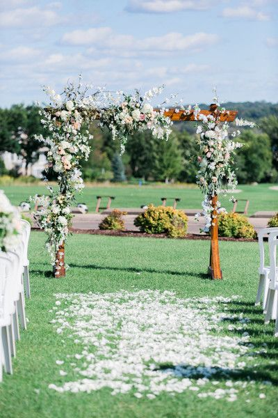 Romantic wedding ceremony arch idea - outdoor ceremony with wooden arch draped in white + pink flowers and greenery  {Dabble Me This}