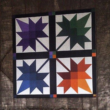 """This """"Four Seasons"""" Barn Quilt feels right at home on the porch of Sherwoods Crossing, a local Amish Quilt store"""