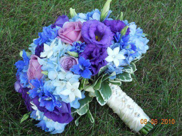 Hand tied bouquet of blue hydrangeas, blue delphinium, lavender roses, purple lisianthus and white stephanotis