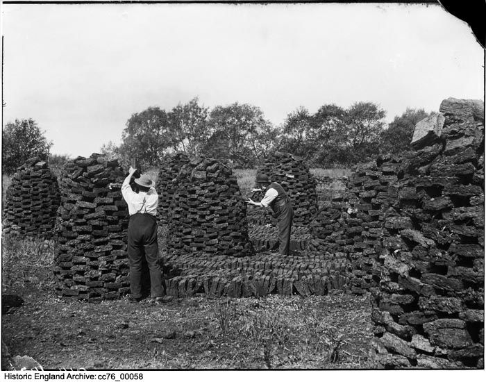 CC76/00058 Two men stacking peat to dry in a field in Shapwick, Somerset. The peat is stacked in such a way so that air can circulate around the blocks and dry them, after which it can then be stored away for later use. 23 Jun 1898
