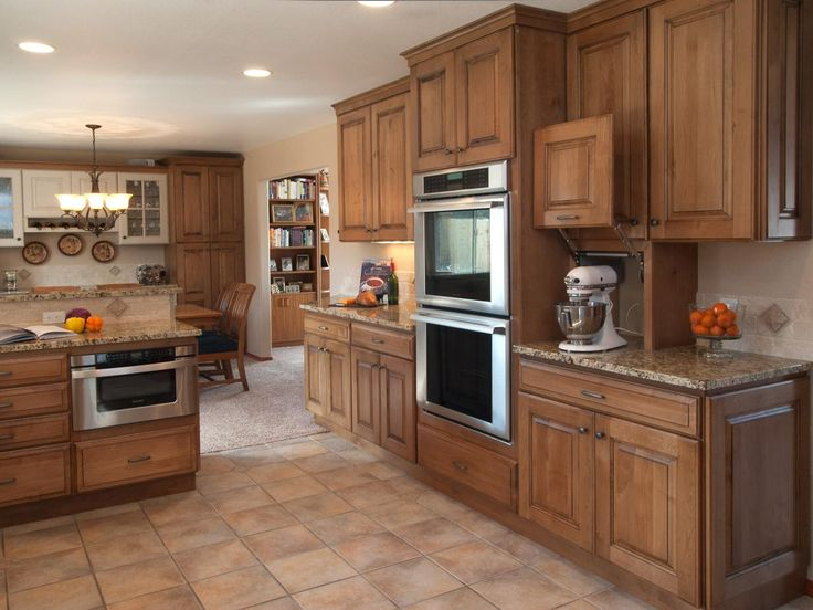 Alder cabinetry with a warm glazed finish offers ample storage space in this transitional kitchen and adjoining dining room. A double oven and microwave are built in, and an appliance garage offers a handy spot to house a stand mixer.