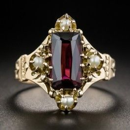 5/8 inch long and lovely, this late-Victorian jewel features an enchanting elongated faceted rectangular garnet imbued with a deep raspberry red hue and embellished on four sides with small lustrous pearls. Hand fabricated in 10K rose gold, circa 1890.