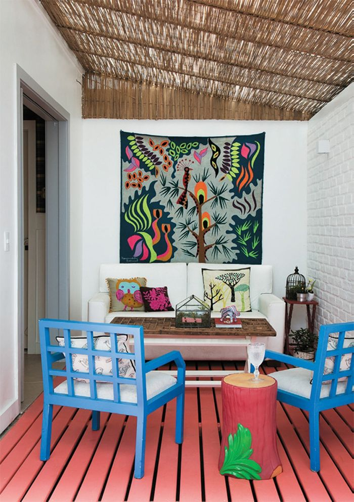 Bamboo overhead, white painted brick wall, cute throw pillows and bold blue  chairs.