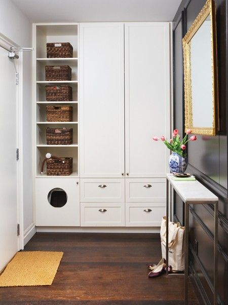 Cubbies holding wicker baskets keep household items within arm's reach from the front door. Sleek white cabinets conceal coats and shoes — even the cat's litter box is kept out of sight with a round hole in the bottom of the cabinet.