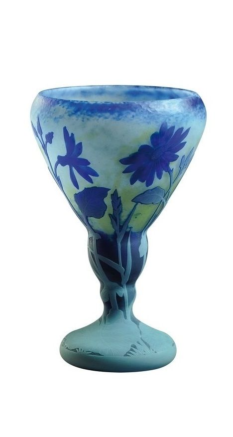 DAUM NANCY A fine carved, martele and etched cameo glass vase. It features gray etched leaves and stems extending upwards to brilliant blue «cinéraria» flowers finely wheel-carved on a mottled martele finish background. Signed in intaglio «Daum Nancy» with the cross of Lorraine. Circa 1914. 9 1/4 in. (23,5 cm) high