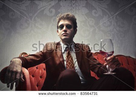 Young elegant man sitting on a velvet sofa and holding a glass of wine