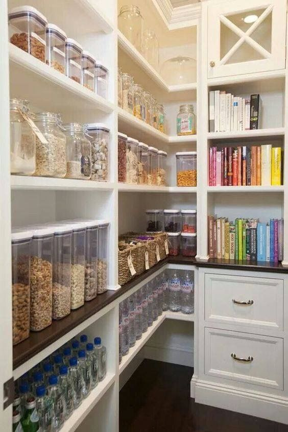 clear food storage containers such as glass jars and cookbooks organized by color helped make this pantry the most popular photo of