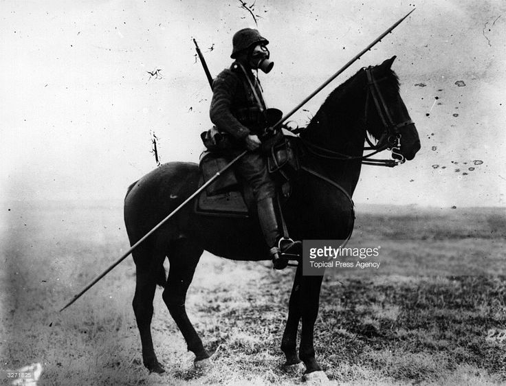 A German cavalryman wearing a gas mask and carrying a long spear or pole - from two different ages of war.
