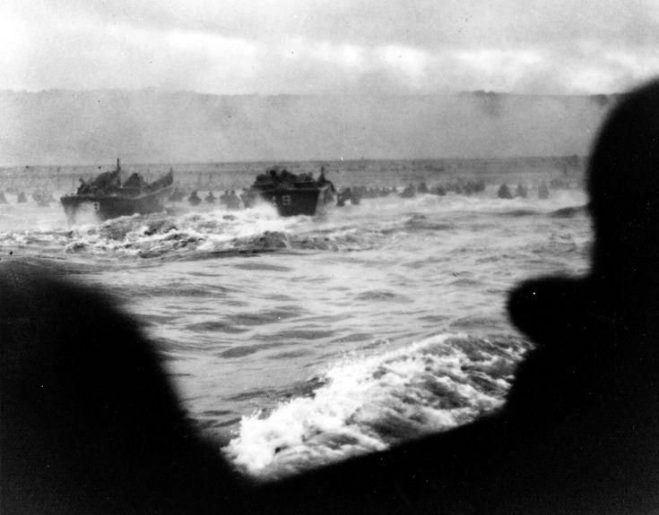 Le 6 juin, Heure H sur Easy Red, les péniches dirigées par les US Coast Guards débarquent des soldats du 16th RCT, entre les Wn 62 et  64, face au plateau où le cimetière américain sera installé après la guerre. Un photographe dans le compartiment-pilote d'une barge saisit la première vague d'assaut jetée dans la mer agitée, la grisaille et la fumée des bombardements. A l'horizon se profilent les hauteurs sombres de la plage.  Les soldats avancent avec de l'eau jusqu'à la taille. On…
