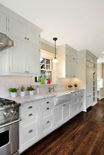 Love white subway tile and shaker cabinets. Love darker wood floors also. Would again still go with a vintage freckled glass drawer pull or something not so mod. Isn't stainless steel out? Not sure about farm sink next to drawer pulls. Love greenery against white subway tile.