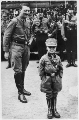Hitler, assembl.ed SA and SS men beam approvingly at a small boy in his Strormtrooper uniform