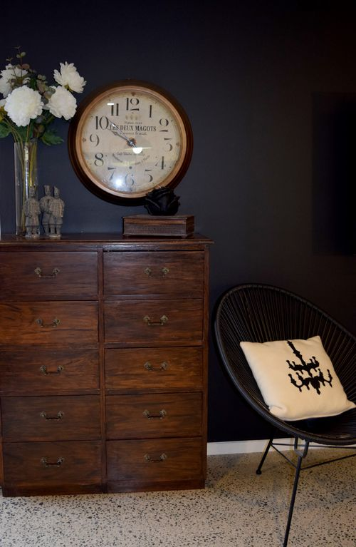 A moody living room wall in Resene All Black becomes a backdrop for a mix of rustic vintage and contemporary furniture.