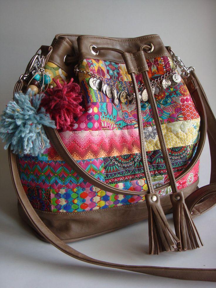 Bolsa feita de tecido de algodão quiltada e detalhes em couro ecológico. Possui duas alças, uma transversal e outra de ombro. Bolsos com zíper na parte de trás e internamente