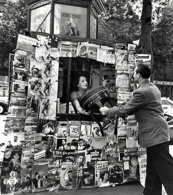 Robert Doisneau : Man Handing Chair into Woman in Newsstand, Paris, 1951.