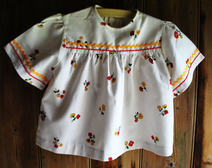 1970s 'Viyella' smock top Age 4 £12 White cotton smock top with red and yellow floral pattern, red and yellow trim detailing, and flared sleeves.  Circa early 1970s Good and vibrant condition