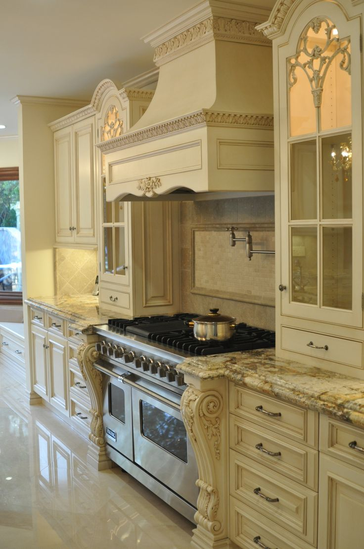 french creamy white kitchen is traditional, ornate with attention to  detail. love the rich granite choice on the cabinets (hood design)