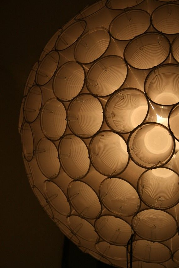 This lampshade is simple and genious. Put together in a geometrical pattern 200 cups form a perfect sphere of 48 cm diameter. The cups are held together only with paper clips, nothing else. Once assembled, the final structure is fairly heavy and surprisingly sturdy.