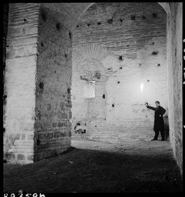 Πύργος του Ανεμά, ο εσωτερικός -σχήματος L- θάλαμος, Μάρτιος 1937. Ένας άγνωστος άνδρας κρατώντας έναν πυρσό φωτογραφίζεται στο εσωτερικό του Πύργου του Ανεμά, στο παλάτι των Βλαχερνών (12ος μ.Χ. αιώνας). Η υψηλή θολωτή οροφή κάνει τον σύντροφό του Artamonoff να φαίνεται μικρός σαν νάνος. Σε μια μικρή κοιλότητα του τοίχου είναι κρυμμένα μια φωτογραφική μηχανή και ένα βιβλίο, πιθανότατα η Βυζαντινή Κωνσταντινούπολη (1899) του Alexander Van Millingen, που χρησίμευε ως οδηγός τους.  ©Nicholas…