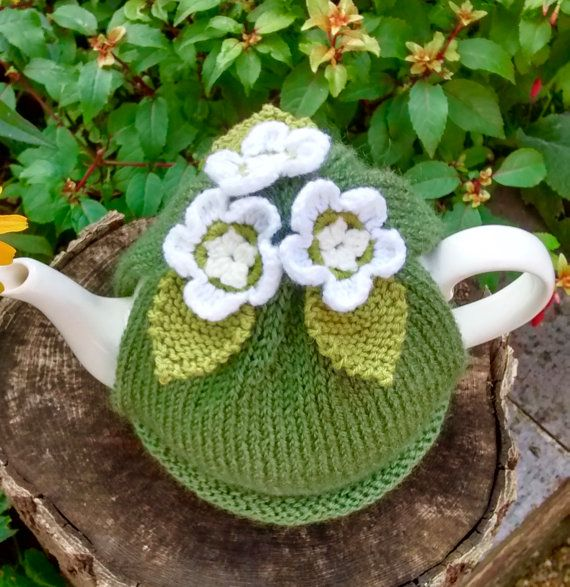 A hand knitted green tea cosy with three crocheted apple blossom flowers attached. The flowers are pale yellow and lime green in the centre and have white petals. The leaves are lime green. Made with Sirdar Wool Rich aran which will keep the teapot nice and warm. Will fit a standard 4 - 6 cup teapot. I would recommend hand washing this item. Do not tumble dry.