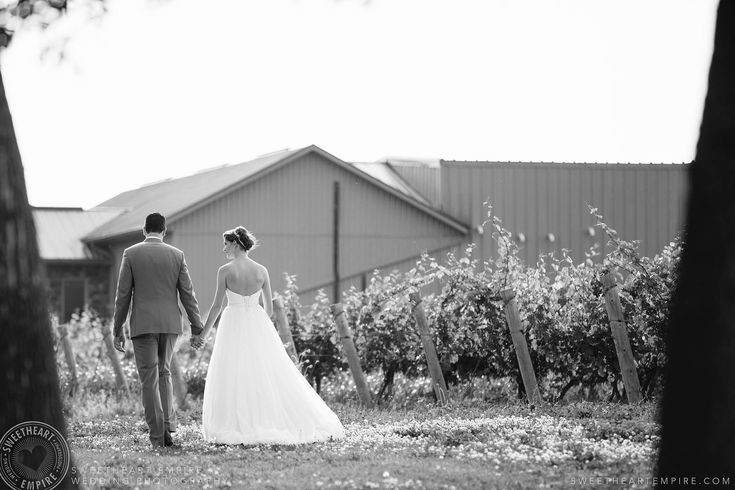 Rockway Vineyards Wedding -Black and white photo of bride and groom walking hand in hand. #sweetheartempirephotography