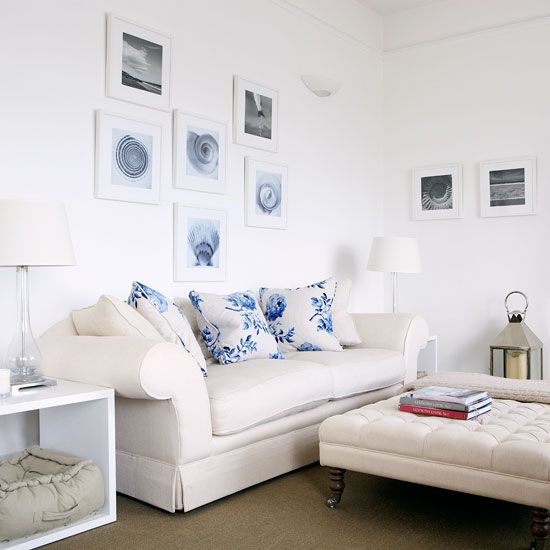 White walls as backdrop for cream sofa, upholstered coffee table, side table and lamps. Coastal pictures and prints on walls.