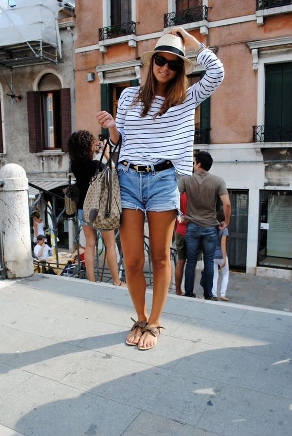 A cute outfit for warm weather while traveling in Europe-- denim shorts with a French-style striped top and a straw fedora.