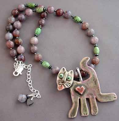 Cat lover necklace with removable pendant to wear as brooch.  Handmade porcelain cat sculpture with pretty pink heart and face details. Turquoise and mauve jasper gemstone necklace.  One of a kind.