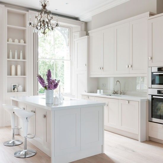 For a timeless look in the kitchen, opt for simple painted cabinetry and kitchen island finished in a subtle white. Here, a display of pretty ceramic vases and an elegant chandelier completes the smart scheme