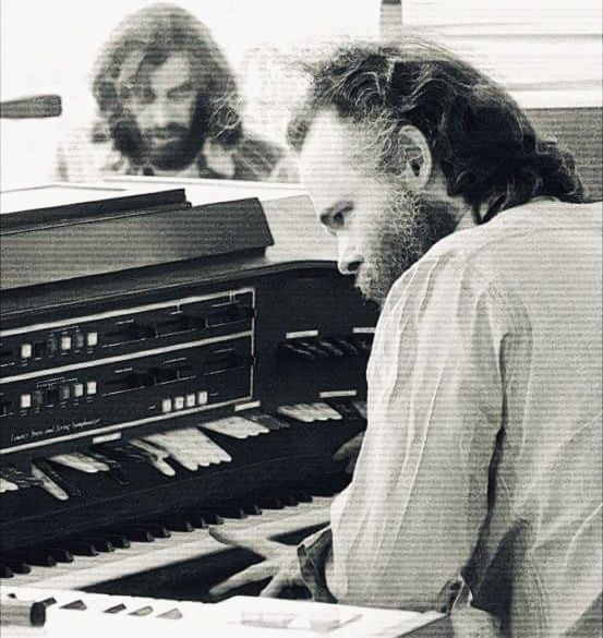 Garth Hudson plays his Lowrey Symphonic Theatre Organ H25-3 (w/Richard Manuel in the background) during The Band concert at Wembley Stadium in 1974. (Photographer: John Scheele)
