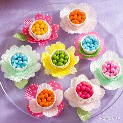 "Create ""flowers"" underneath your treats by cutting white and yellow baking cups into different flower shapes and layering them with mini baking cups."