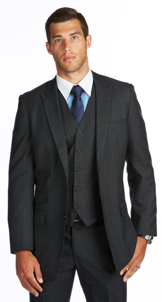 Alex Rance wearing a Charcoal Prince of Wales silver check with navy window pain, with a peak lapel, two black buttons, straight jacket pocket flaps and ticket pocket. Flat front tapered trouser with side pockets and two rear pockets. Waistcoat is a five button with jets. #suit #bespoke #bespokesuit #customsuit #wedding #groom #groomsmen #waistcoat #threepiecesuit #handsome #dapper #mensstyle #mensfashion #gentlemen #gentleman #chivalry #charcoalsuit #tie #navytie #polkadot #polkadottie